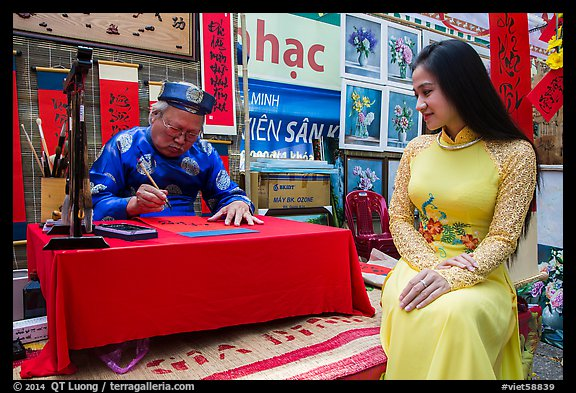 Caligrapher draws lunar new year greetings for beautiful woman in ao ai. Ho Chi Minh City, Vietnam (color)