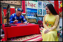 Caligrapher draws lunar new year greetings for beautiful woman in ao ai. Ho Chi Minh City, Vietnam ( color)