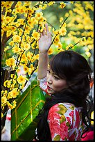 Woman next to Tet (Lunar New Year) decorations. Ho Chi Minh City, Vietnam ( color)