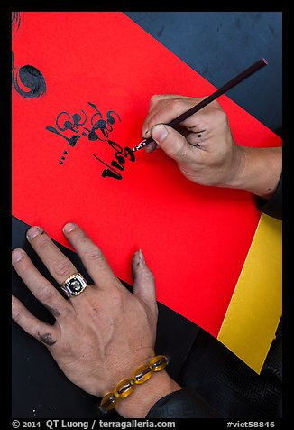 Hands drawing Tet greetings in ornamented characters. Ho Chi Minh City, Vietnam (color)