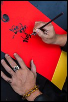 Hands drawing Tet greetings in ornamented characters. Ho Chi Minh City, Vietnam ( color)