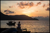 Silhouetted woman watching sunrise from Wharf 914, Con Son. Con Dao Islands, Vietnam ( color)