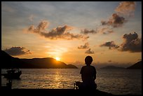 Sitting woman in silhouette and sunrise, Con Son. Con Dao Islands, Vietnam ( color)