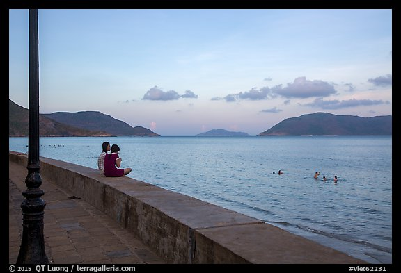 Young women sitting on seawall, evening, Con Son. Con Dao Islands, Vietnam (color)