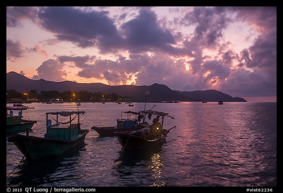 Men with light on fishing boat at dawn, Con Son harbor. Con Dao Islands, Vietnam (color)