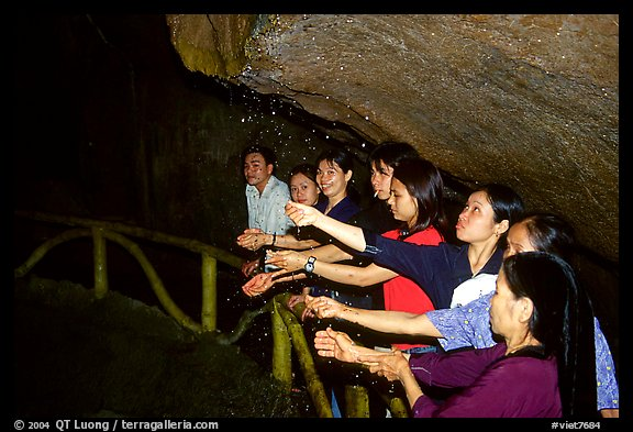 Women catch the water seeping from Tan Thanh Cave, said to have mirculous properties. Lang Son, Northest Vietnam (color)