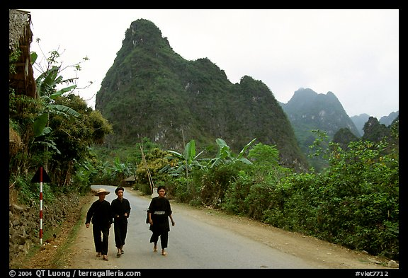 Villagers in traditional garb walking down the road with limestone peaks in the background, Ma Phuoc Pass area. Northeast Vietnam (color)
