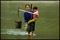 Tay Woman carrying child and water buckets across river. Northeast Vietnam (color)