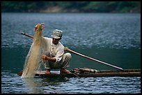 Fisherman retrieves net from a dugout boat. Northeast Vietnam ( color)