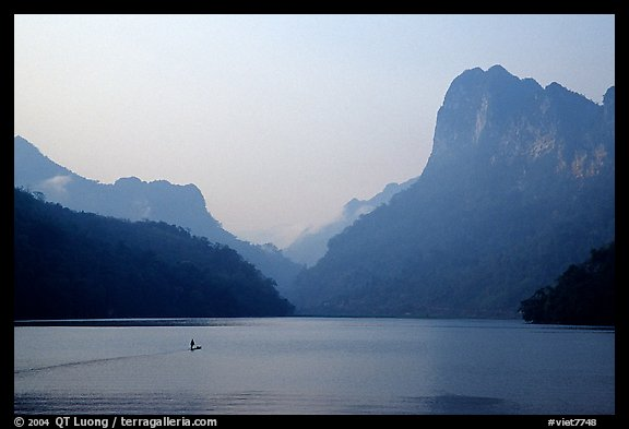 Dugout boat in Ba Be Lake, surrounded by tall cliffs, early morning. Northeast Vietnam (color)