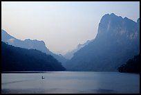 Dugout boat in Ba Be Lake, surrounded by tall cliffs, early morning. Northeast Vietnam ( color)
