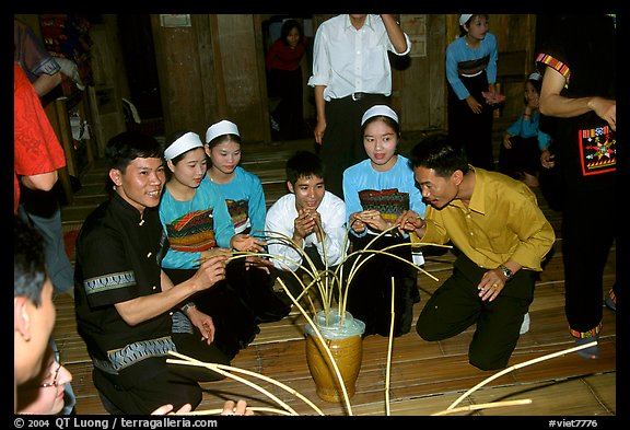 Thai women and guests drinking rau can alcohol with long straws, Ban Lac, Mai Chau. Northwest Vietnam (color)