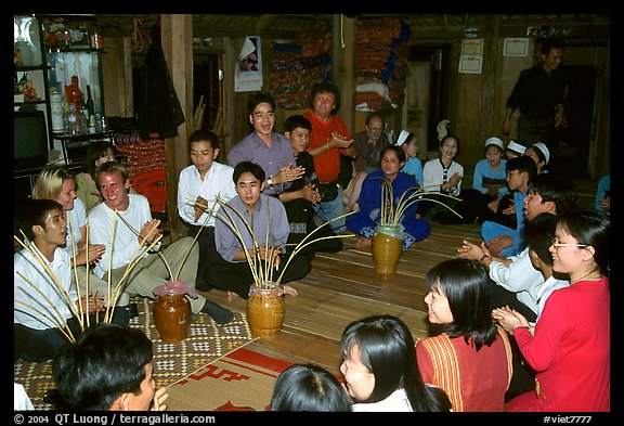 Guests in a thai house gather around jars of rau can alcohol, Ban Lac, Mai Chau. Northwest Vietnam (color)