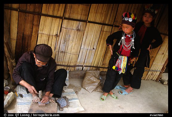 Black Dzao children look at a man  making the decorative coins used on their hats, between Tam Duong and Sapa. Northwest Vietnam (color)