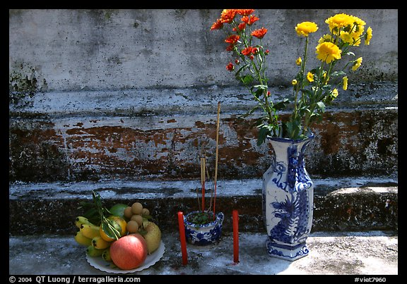 Flowers, fruit, and incense offered on a grave. Ben Tre, Vietnam