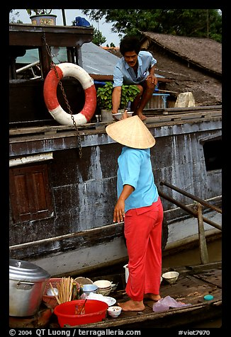Passsing a bowl of pho from boat to boat. Can Tho, Vietnam (color)
