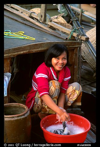 Woman doing laundry on live-aboard boat, the cheapest and most convenient housing in the Delta, near Can Tho. Vietnam (color)