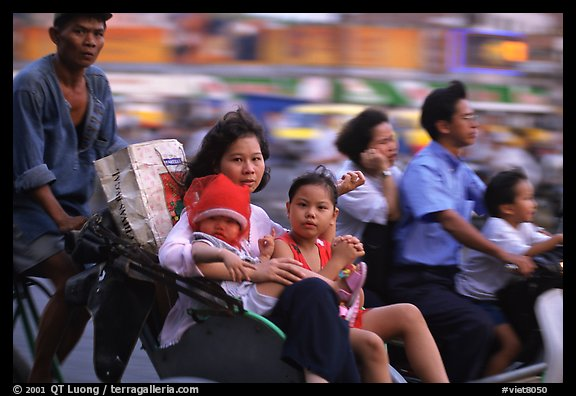 Wheels are seldom for single drivers: families on cyclo and motorbike. Ho Chi Minh City, Vietnam (color)