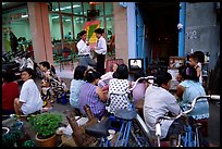 Watching TV on the street with the neighboors. Ho Chi Minh City, Vietnam
