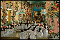 The noon ceremony, attended by priests inside the great Cao Dai temple. Tay Ninh, Vietnam (color)