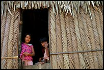 Children pear through a traditional hut. Hong Chong Peninsula, Vietnam