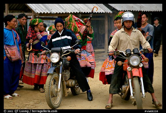 Flower Hmong women getting a ride on all-terrain russian-made motorbikes to the sunday market. Bac Ha, Vietnam (color)
