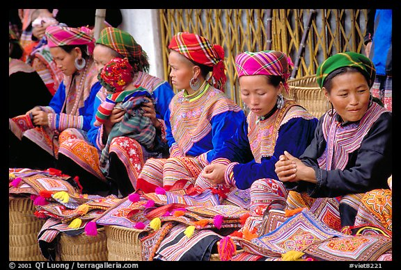 Women sell the colorful garnments after which the Flower Hmong are named. Bac Ha, Vietnam (color)