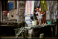 Children peering from their waterfront house. Can Tho, Vietnam ( color)